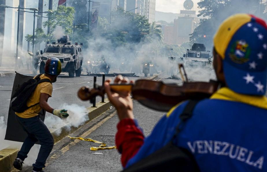Interprétant l'hymne vénézuélien, Wuilly Arteaga avance le 8mai vers les militaires sous une pluie de cartouches de gaz lacrymogènes. Il tient à rendre hommage à un musicien de 17ans tué quelques jours avant lors d'une manifestation. | 2 juin 2017
