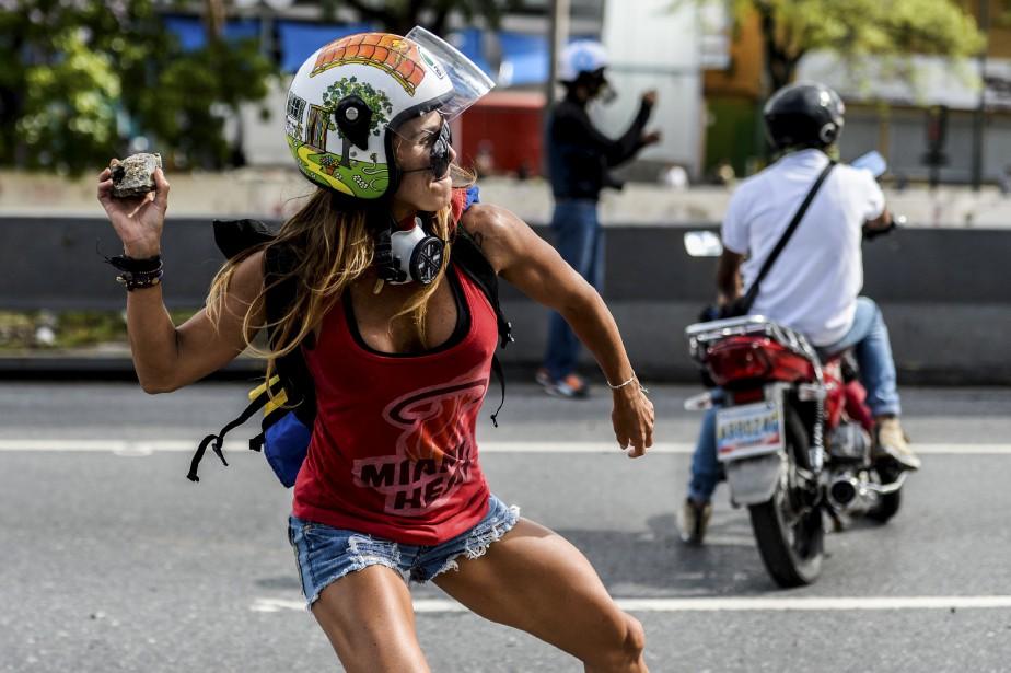 Muscles parfaitement dessinés, Caterina Ciarcelluti, qui manifeste en short et coiffée d'un casque de moto, lance des pierres vers les militaires ce 1ermai. Cette professeure de  fitness  de 44ans devient virale et rapidement les Vénézuéliens la surnomment «Wonder Woman». | 2 juin 2017