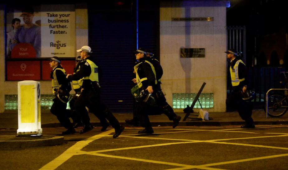 Des policiers courent pour gagner le pont de Londres. (Photo Hannah McKay, Reuters)