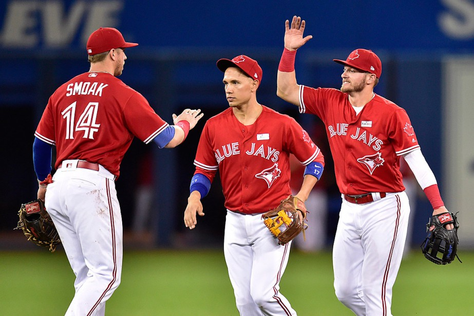 Justin Smoak, Ryan Goins et Josh Donaldson célèbrent... (PHOTO FRANK GUNN, LA PRESSE CANADIENNE)