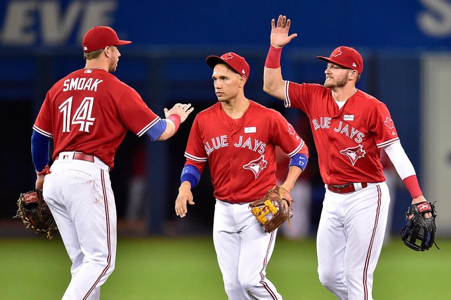 Justin Smoak, Ryan Goins et Josh Donaldson célèbrent... (PHOTO FRANK GUNN, LA PRESSE CANADIENNE)