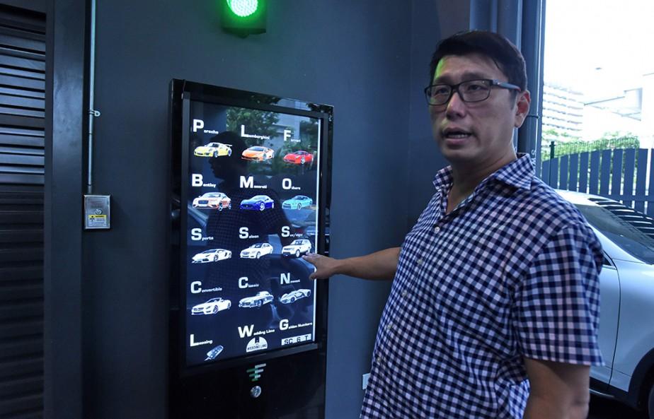 Les clients au pied de l'édifice peuvent choisir la voiture qu'ils désirent à partir d'un écran tactile et l'obtenir en moins de deux minutes. (Photo ROSLAN RAHMAN, AFP)