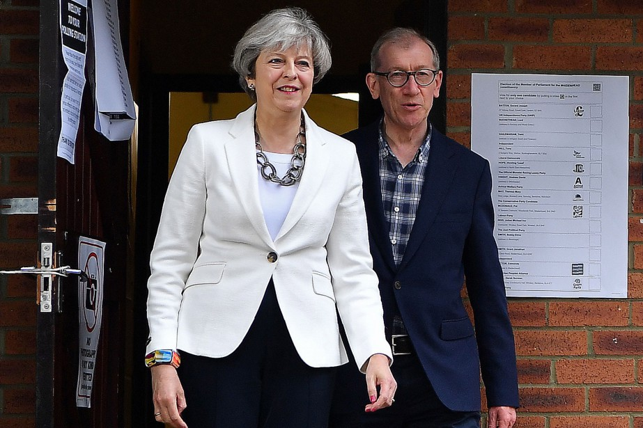 Theresa May, accompagnée de son mari Philip, quitte... (PHOTO AFP)