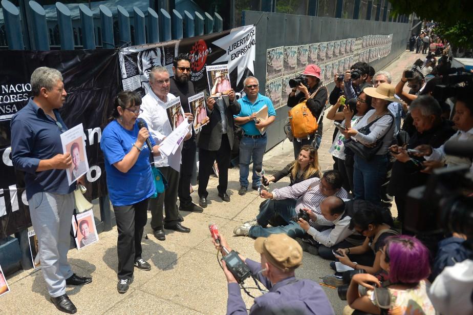Des journalistes tiennent des photos de collègues récemment... (PHOTO PEDRO PARDO, ARCHIVES AGENCE FRANCE-PRESSE)