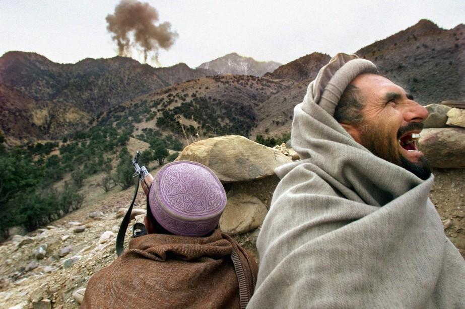 Des combattants afghans observent des bombardements américains effectués... (ARCHIVES AP)