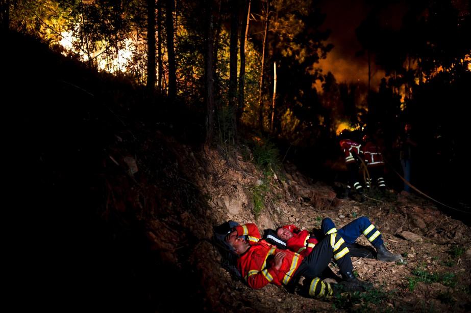 Des pompiers se reposent un peu pendant leur combat contre les flammes. (AFP, Patricia De Melo Moreira)