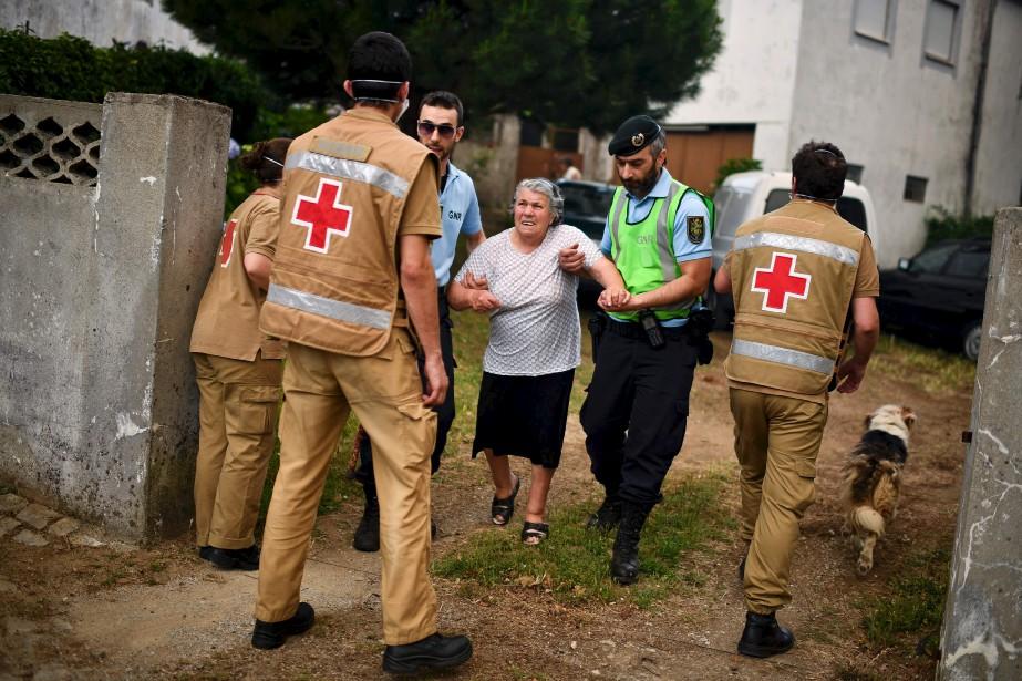 Des membres de la Croix-Rouge évacuaient dimanche des résidents de Torgal,Castanheira de Pera. (AFP, Patricia De Melo Moreira)