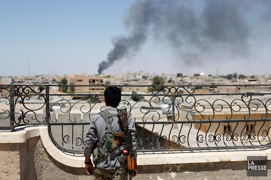 Un soldat kurde regarde la fumée s'élever dans... (Archives, La Presse)