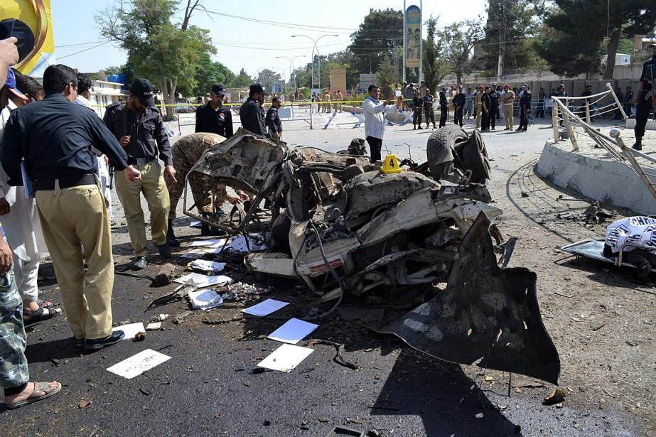 Des enquêteurs examinent les restes de la camionnette... (PHOTO ARSHAD BUTT, ASSOCIATED PRESS)