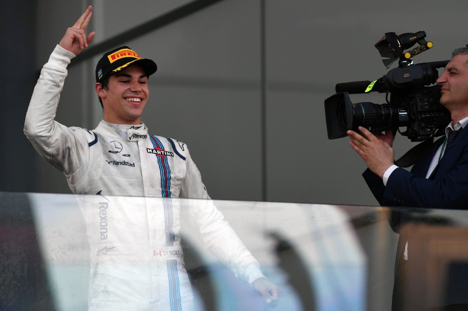 Third placed Williams' Canadian driver Lance Stroll celebrates...