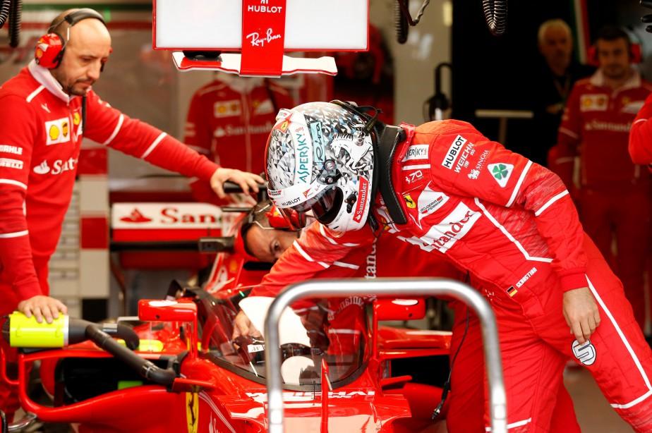 Sebastian Vettel s'apprêtant à prendre place dans sa Ferrari. (REUTERS)