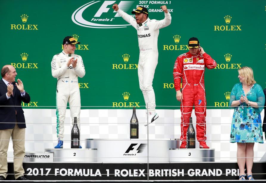 Lewis Hamilton célèbre sa victoire sur le podium; Valteri Bottas applaudit et Kimi Raïkkönen se gratte l