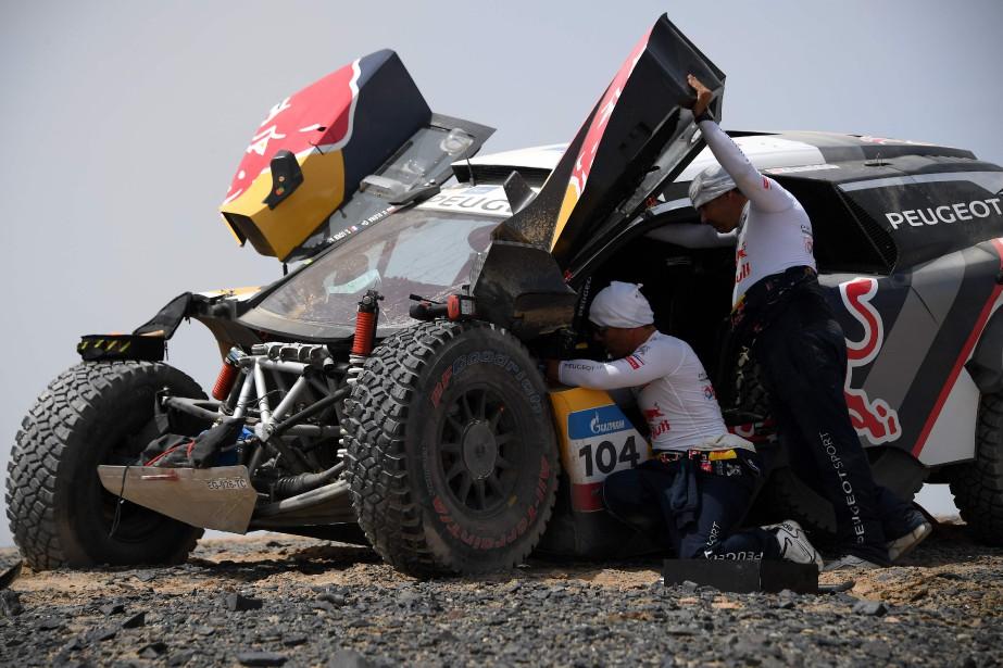 Les Français Sébastien Loeb et Daniel Éléna constatent les dégâts après avoir foncé à toute vitesse dans un trou. L'épreuve lie les villes d'Urumqi et de Hami, dans le désert de Gobi, en Chine. (AFP)