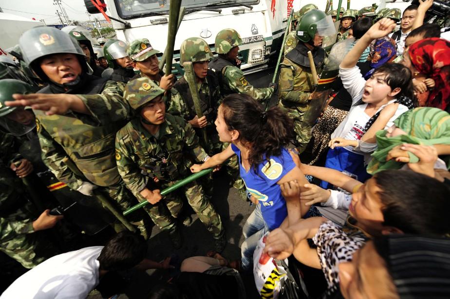 Des femmes ouïghoures manifestant pour les droits de cette ethnie musulmane et turcophone, sont confrontées par la police chinoise le 7 juillet 2009. La violence s'est résorbée mais les tensions inter-ethniques demeurent élevées dans cette région isolée de Chine. (AFP)
