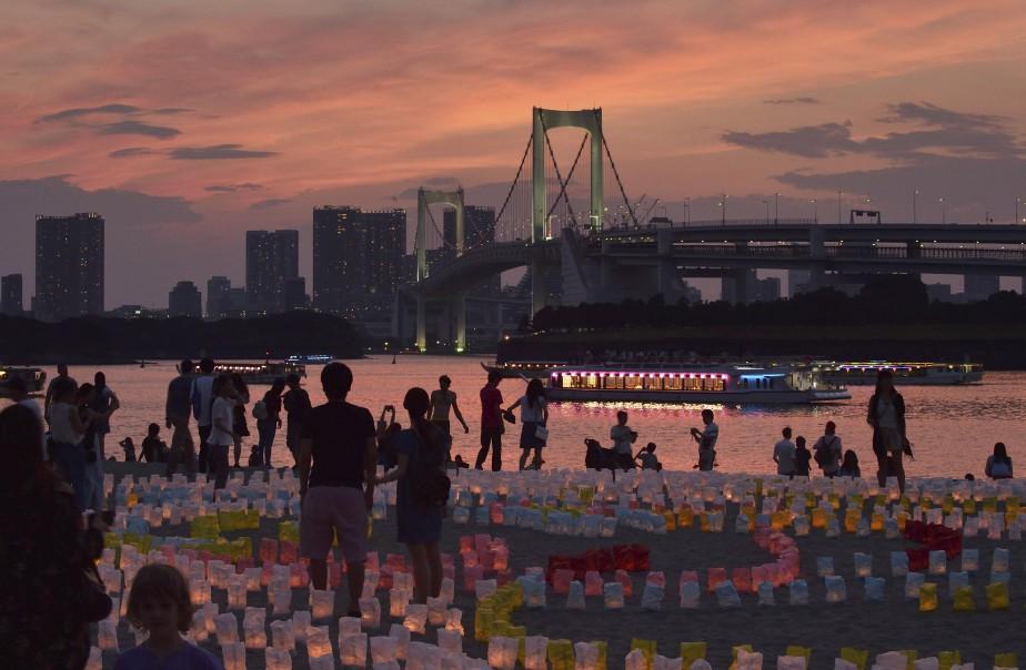 Des visiteurs observent les lanternes sous un coucher de soleil... | 2017-07-17 00:00:00.000