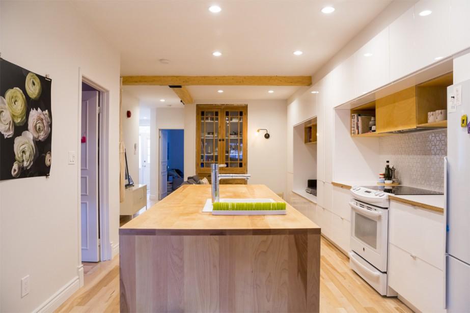 La cuisine, avec son grand îlot central en bois, constitue le coeur de cette résidence. L'occupante peut cuisiner et jeter un coup d'oeil à sa fille qui joue, peu importe où elle se trouve. (photo Marie-Christine Gobeil, collaboration spéciale)