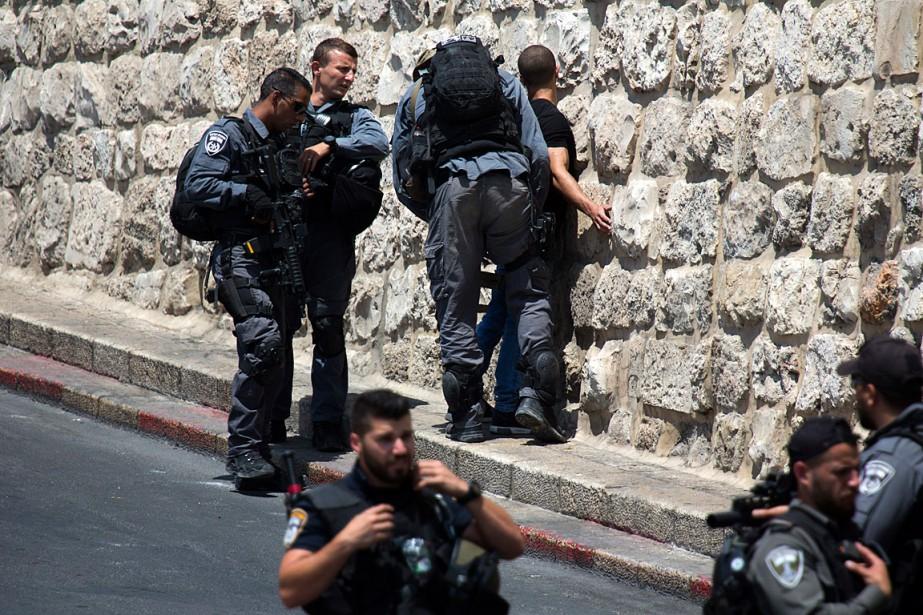 Des policiers israéliens ont arrêté un jeune Palestinien... (PHOTO ARIEL SCHALIT, ASSOCIATED PRESS)