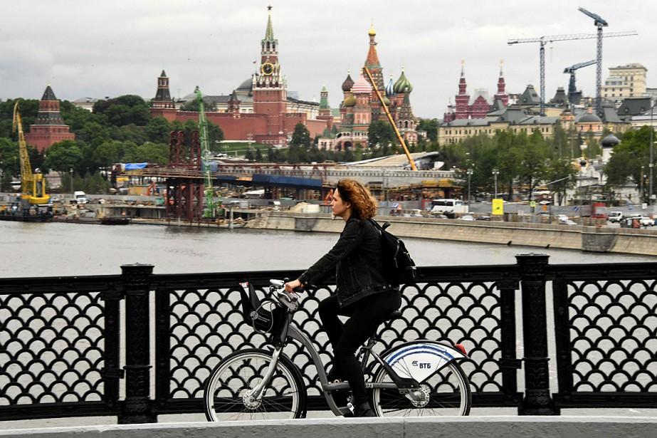 Une cycliste traverse un pont de Moscou, le... (PHOTO KIRILL KUDRYAVTSEV, AGENCE FRANCE-PRESSE)