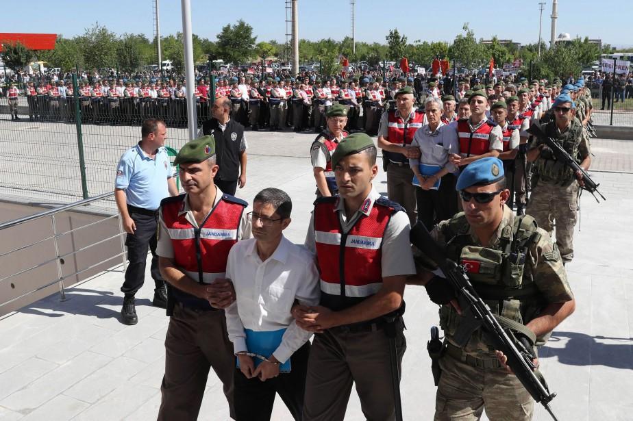L'homme d'affaires Kemal Batmaz(première rangée, au centre) et... (PHOTO ADEM ALTAN, AFP)