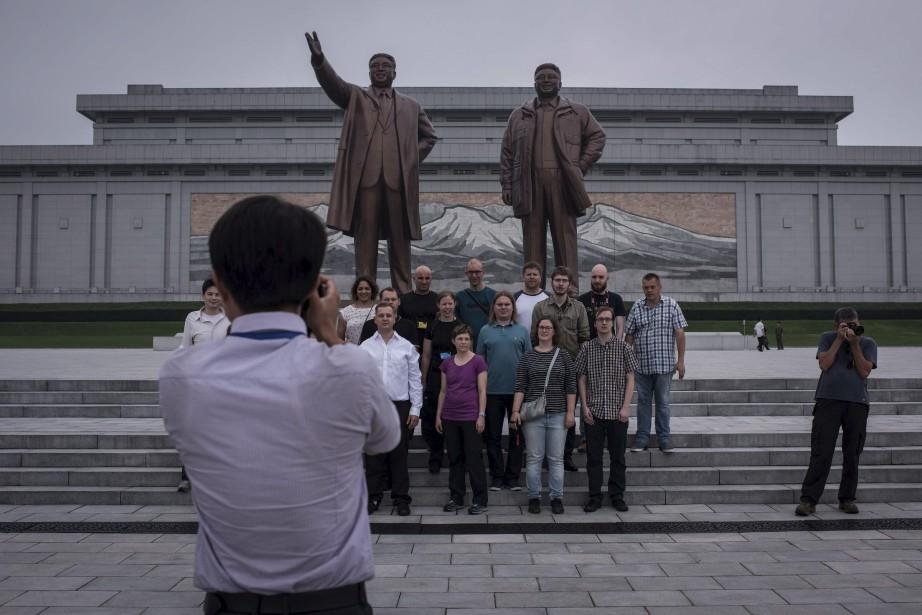 Un groupe de touristes pose devant les statues... (Photo Ed Jones, archives AFP)