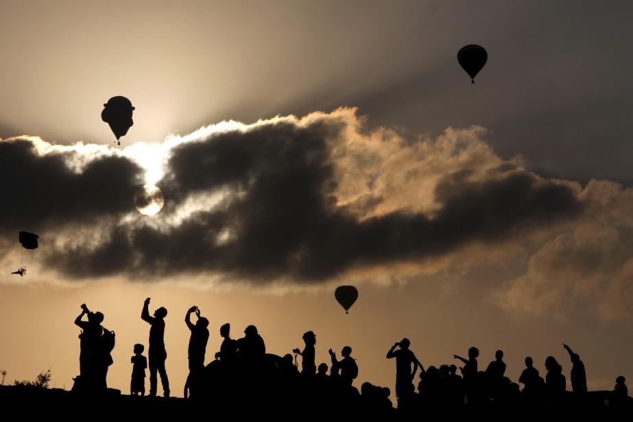 Des Israéliens prennent des photos de montgolfières lors du Festival de montgolfière de Gilboa, près d'Eïn Harod, en Israël. | 4 août 2017
