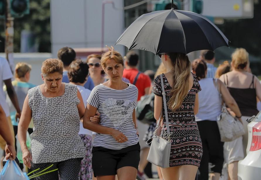 Un conseil toujours judicieux par grande chaleur : protéger sa peau sous un parapluie, comme le fait cette jeune femme à Bucarest, en Roumanie, où la température a grimpé à 42 degrés Celcius, samedi. | 5 août 2017