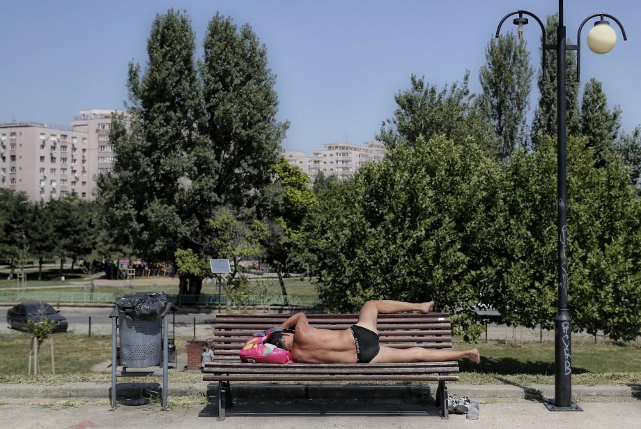 Les météorologues roumains ont émis un avertissement de chaleur extrême valide pour les deux prochains jours. Près du Palais présidentiel de Bucarest, cet homme a simplement décidé de combattre la chaleur en se couchant sur un banc pour éviter de trop bouger. | 5 août 2017