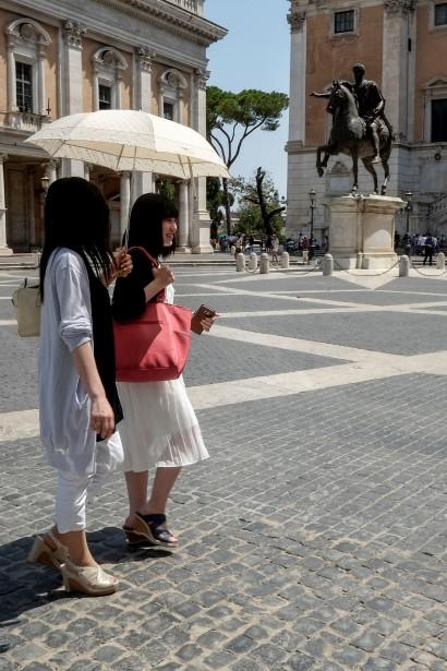 Ne voulant rien manquer des attraits touristiques de Rome, ces deux touristes ont toutefois pris leurs précautions, s'abritant sous un parapluie pour parcourir la Ville éternelle. | 5 août 2017