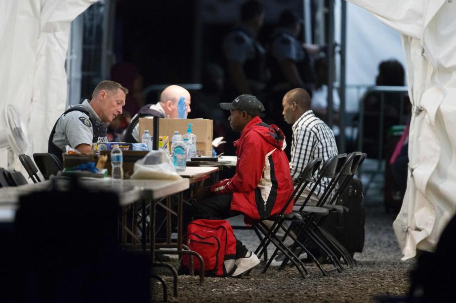 Sous une grande tente, des policiers fédéraux procèdent... (Photo AFP)