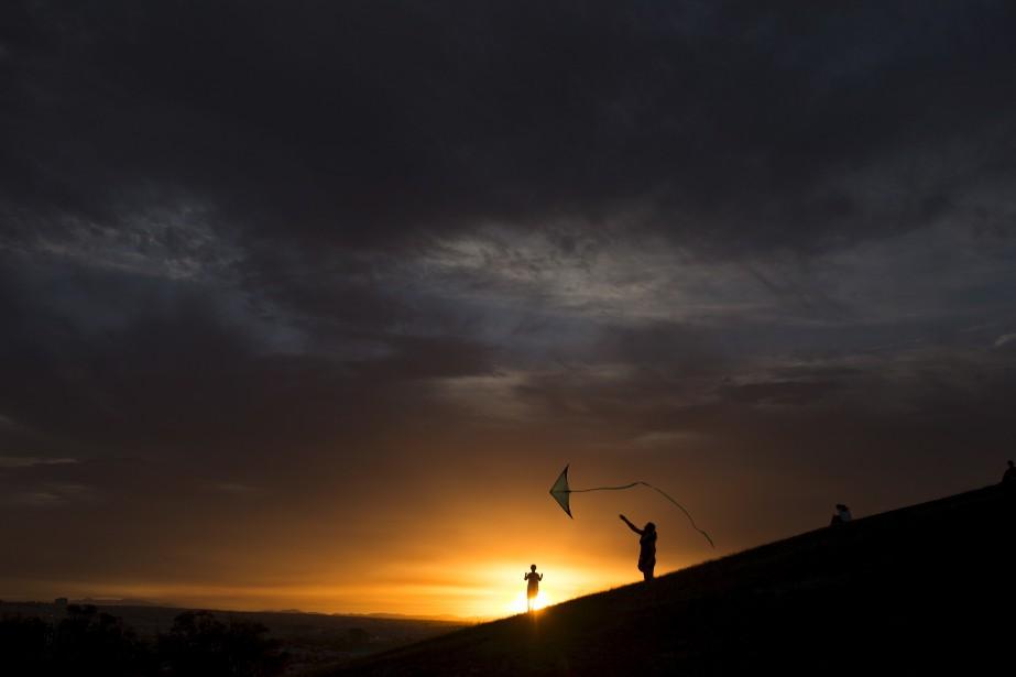 Un homme fait voler un cerf-volant lors du coucher de soleil, au parc Tio Pio, à Madrid.   8 août 2017