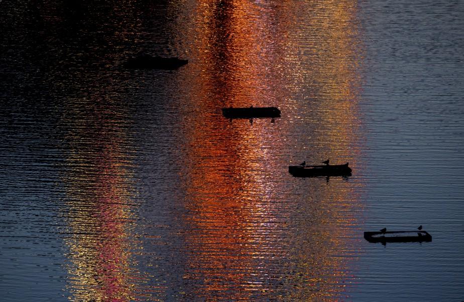 Les lumières d'une fête foraine sont reflétées dans un lac au parc Olympia, à Munich, en Allemagne.   8 août 2017