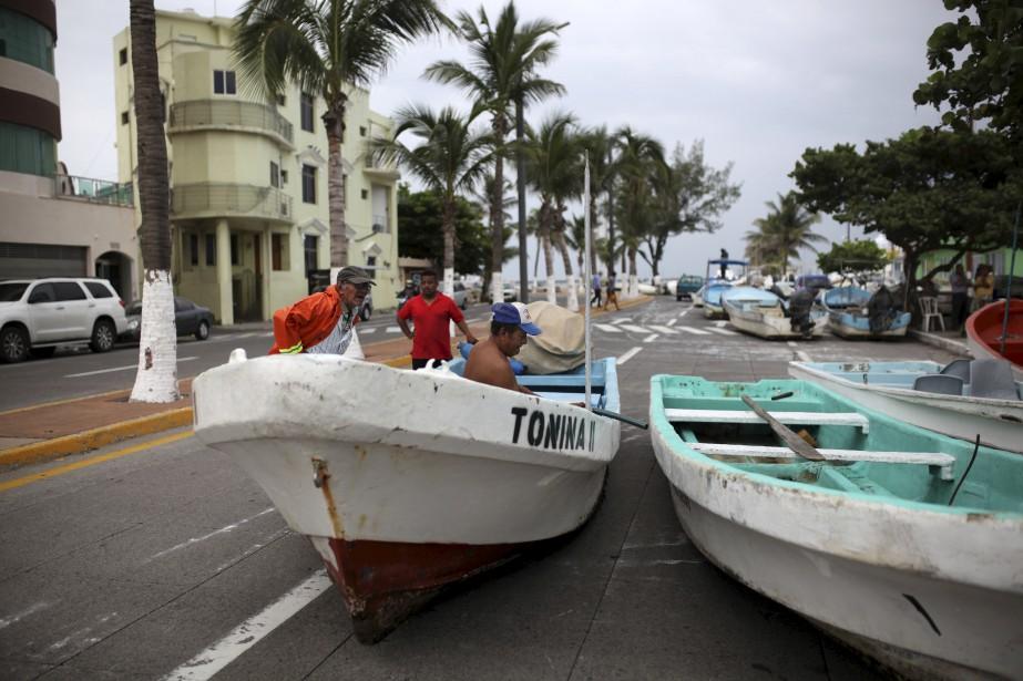 Des pêcheurs déplacent leurs bateaux sur une route côtière afin de se protéger, avant l'arrivée de la tempête tropicale Franklin, dans le port de Veracruz, au Mexique.   9 août 2017