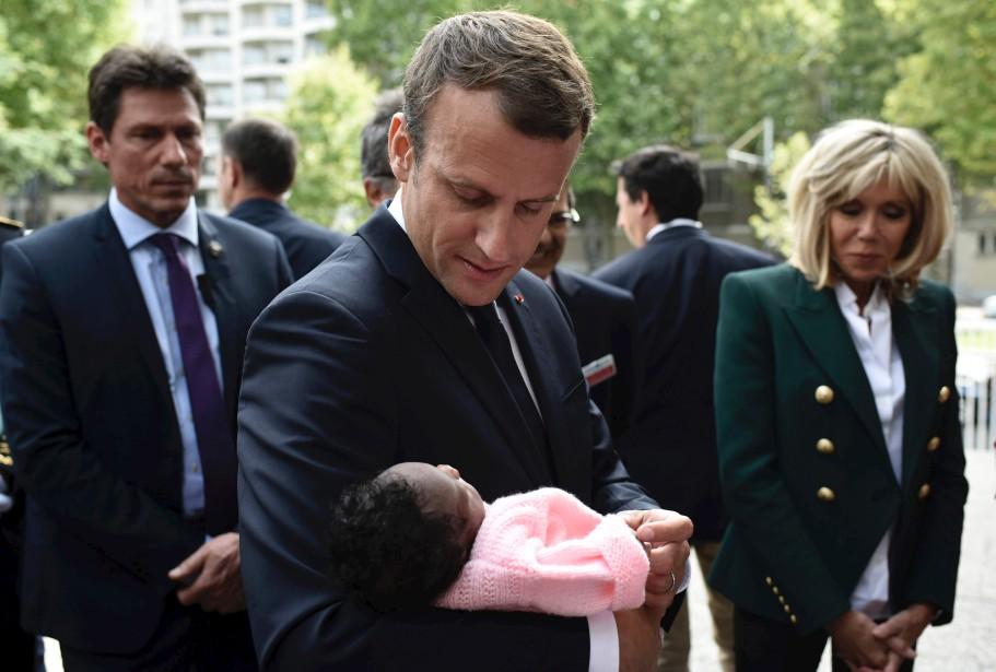 Le président français, Emmanuel Macron (au centre), accompagné par sa femme, Brigitte Macron (à droite), prend un nouveau-né dans ses bras, alors qu'il visite l'hôpital pédiatrique Robert-Debré, à Paris.   9 août 2017