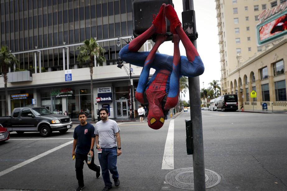 Rashad Rouse, 27 ans, est suspendu à un poteau de signalisation, vêtu d'un costume de Spiderman, afin d'attirer l'attention des touristes sur le boulevard Hollywood, à Los Angeles.   9 août 2017