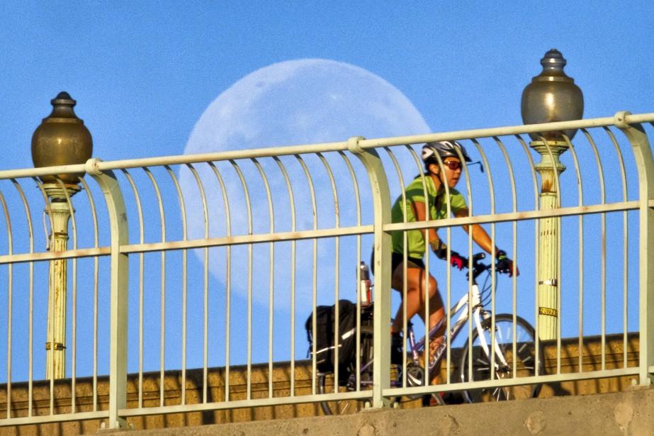 Une cycliste passe devant la lune et traverse le pont Francis Scott Key, à Washington.   9 août 2017