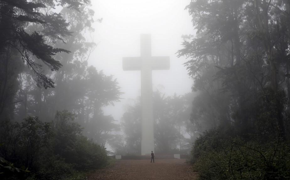 Un visiteur marche devant une croix envahie de brouillard, au mont Davidson, à San Francisco.   11 août 2017