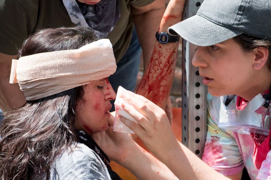 Une jeune femme reçoit les premiers soins aprèsqu'une voiture ait foncé dans la foule qui manifestait à Charlottesville, samedi. | 12 août 2017