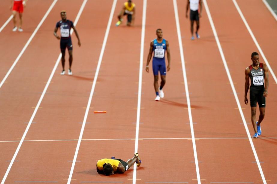 Usain Bolt s'est effondré sur le piste.... (Photo Reuters)