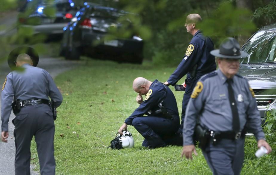 Des policiers se trouvent près du lieu de l'écrasement d'un hélicoptère aux environs de Charlottesville. | 12 août 2017