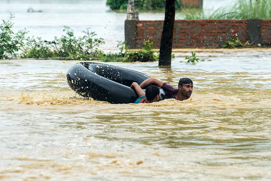 Des Népalais tentent de rejoindre la terre ferme... (PHOTO MANISH PAUDEL, AGENCE FRANCE-PRESSE)