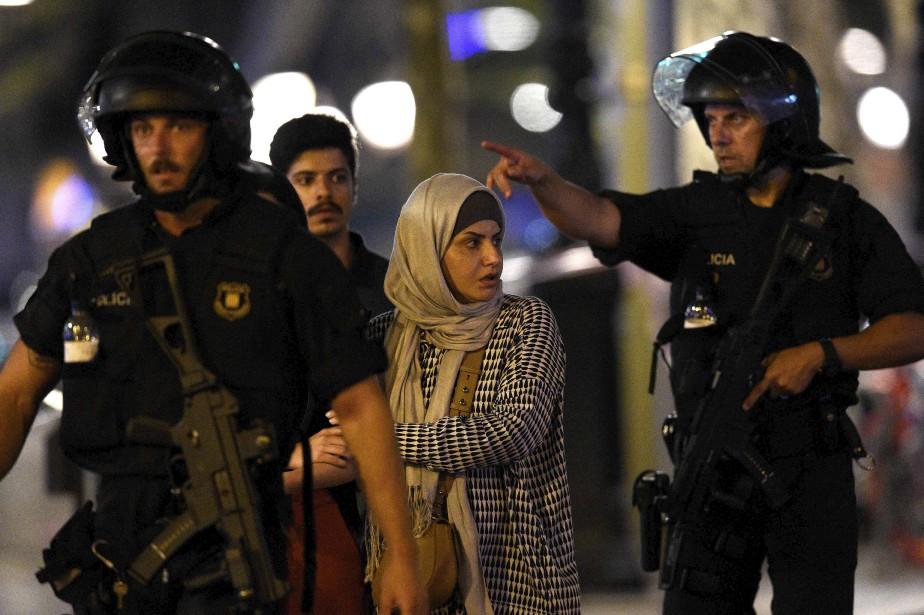 Des clients d'un magasin sont escortés par des policiers hors de la zone de l'attentat. (AFP, LLUIS GENE)