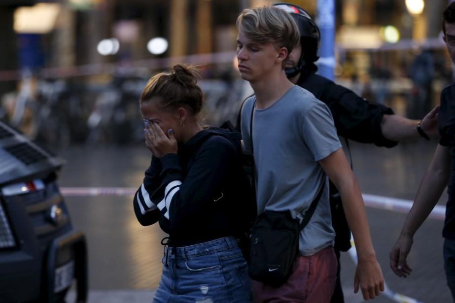 Des touristes visiblement sous le choc sont escortés hors de la zone où s'est produit l'attentat, bouclée par les policiers. (AFP, PAU BARRENA)