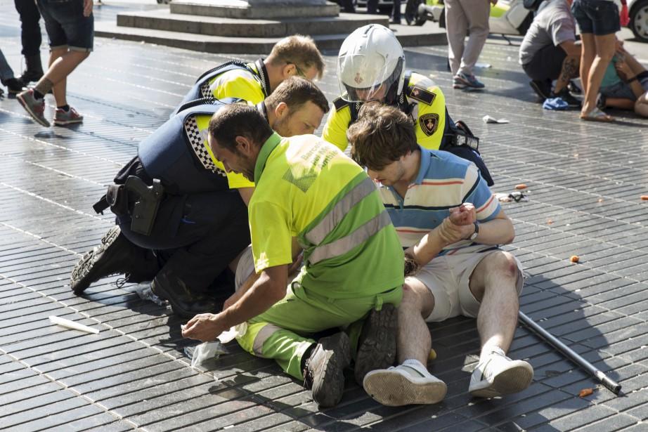 Un policier et deux hommes viennent en aide à une personne happée par le véhicule. (AFP, Nicolas Carvalho Ochoa)