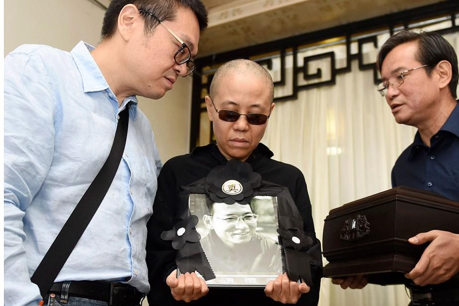 Liu Xia tient un portrait de son époux... (PHOTO ARCHIVES ASSOCIATED PRESS)