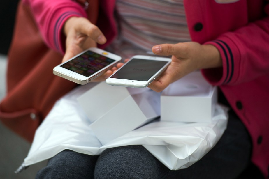 Une femme compare son nouveau iPhone6 avec son... (PHOTO JOHANNES EISELE, ARCHIVES AGENCE FRANCE-PRESSE)