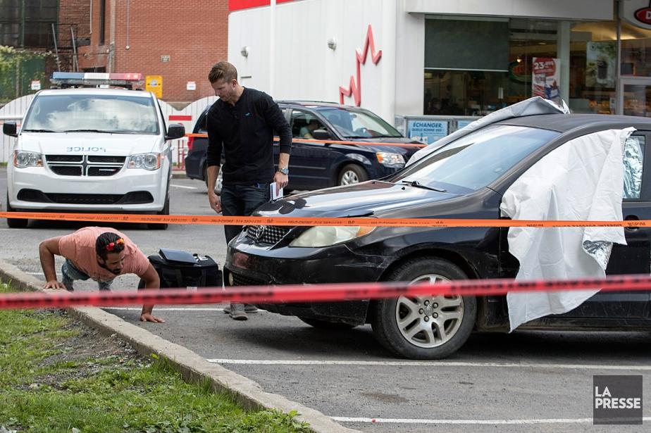 Deux enquêteurs examinent la voiture garée dans un... (PHOTO IVANOH DEMERS, ARCHIVES LA PRESSE)