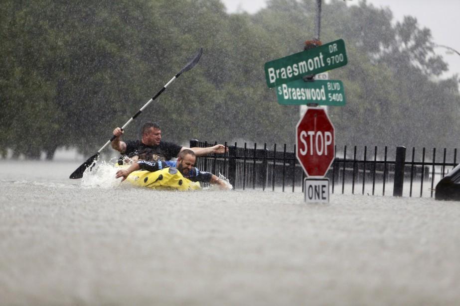 Deux kayakistes tentant de ramer contre le courant provoqué par les pluies torrentielles de<em>Harvey</em>à Houston. (AP, Mark Mulligan)