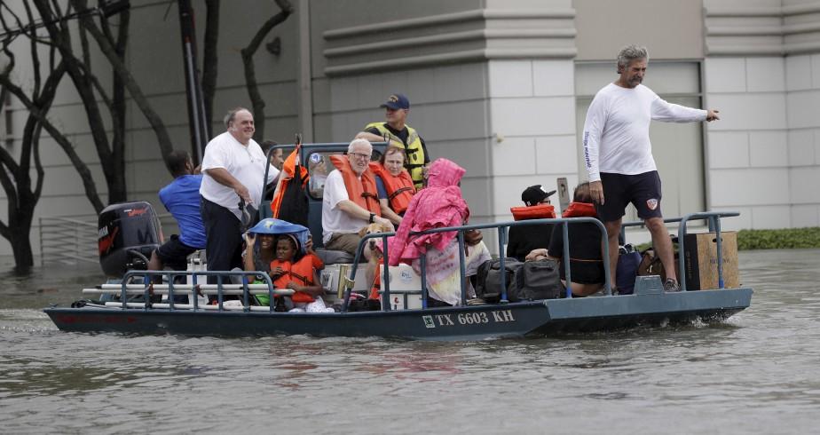 Des résidents sont évacués de leur maison submergée à Houston. (AP, David J. Phillip)