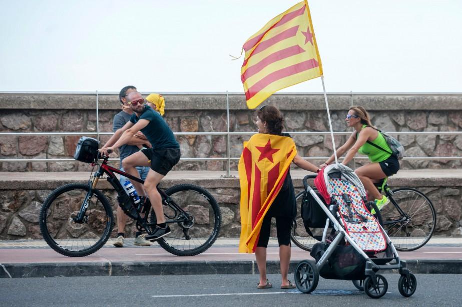 Un homme à vélo regarde une manifestante pro-indépendantiste... (Photo GARI GARAIALDE, AFP)