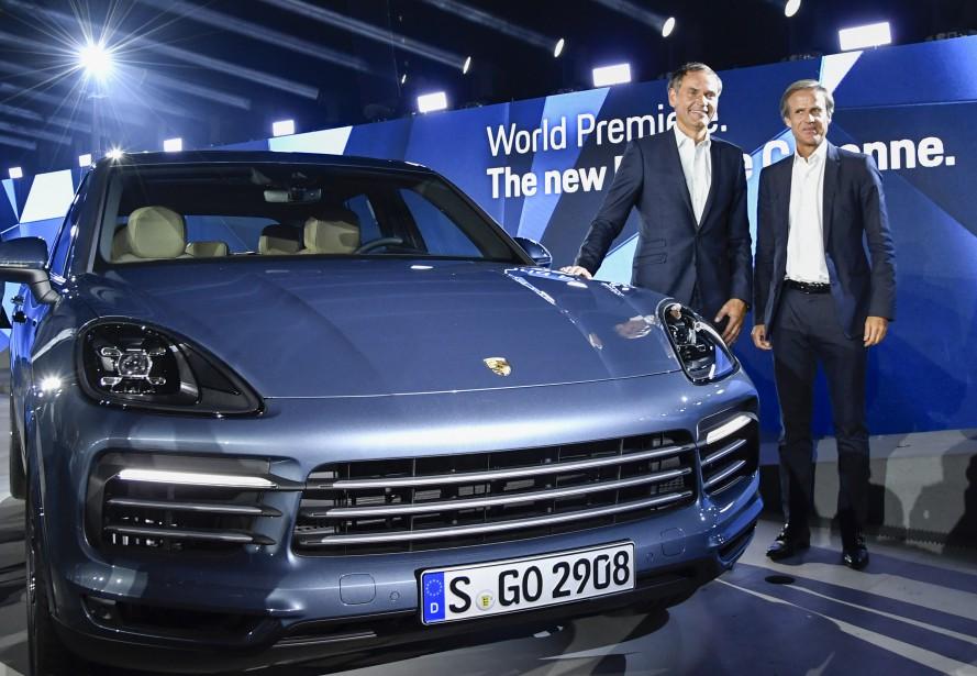 Le pdg de Porsche, Oliver Blume (à g.) et le patron du design Michael Mauer, posent à côté du Porsche Cayenne 2019 à Stuttgart au siège social du constructeur allemand. (Photo : AFP)